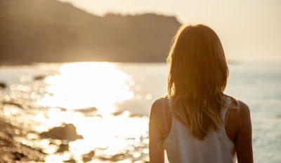 Mulher olhando paisagem na praia